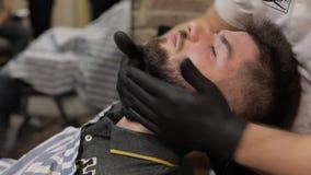 Клиент с черной бородой во время бороды брея в парикмахерской Выхольте, мужеский видеоматериал