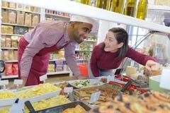 Клиент указывая на блюдо с продажами ассистентскими на гастроном против стоковые изображения
