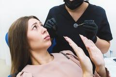 клиника зубоврачебная Прием, рассмотрение пациента Забота зубов Молодая женщина чувствует страх на дантисте стоковые фото