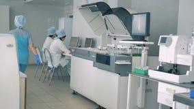 Клиническая лаборатория с анализировать оборудование и несколько работников в ем сток-видео
