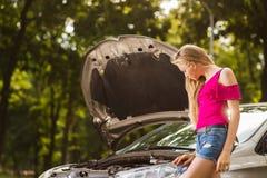 Клобук автомобиля девушки Blondy унылый близко открытый стоковые изображения rf