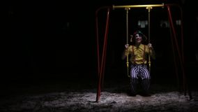 Клоун едет низкие качания детей в темноте сток-видео