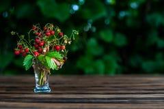 клубника букета дикая в прозрачных пребываниях стопки на коричневом деревянном столе с зелеными листьями на задней части, с указа стоковые фотографии rf