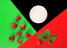 Клубника, молоко и листья зеленого цвета на покрашенной предпосылке стоковые фото