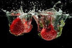 Клубники брызгая в воду Стоковая Фотография