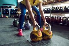 Клуб Kettlebell Девушка получает готовой сделать разминку с весами, нажимает длительный цикл стоковое фото rf