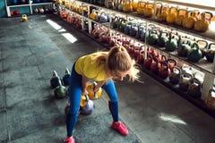 Клуб Kettlebell Девушка получает готовой сделать разминку с весами, нажимает длительный цикл стоковое изображение