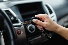 Ключи автомобиля в руке девушки в интерьере автомобиля Стоковые Фотографии RF