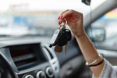 Ключи автомобиля в руке девушки в интерьере автомобиля Стоковые Изображения RF