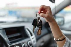 Ключи автомобиля в руке девушки в интерьере автомобиля Стоковые Изображения