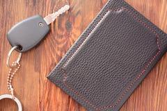 Ключи и документы автомобиля в кожаной крышке на предпосылке деревянной текстуры стоковые изображения