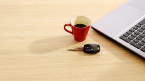 Ключ автомобиля и красные кофейная чашка и labtop на деревянных предпосылках таблицы Стоковое фото RF