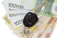 Ключ автомобиля на предпосылке денег евро на белой предпосылке Стоковая Фотография