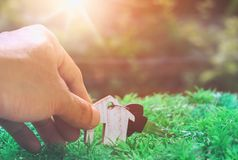 Ключ в руке и дом моделируют, планируют деньги сбережений монеток стоковая фотография