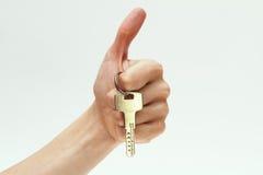 Ключ в руке на белой предпосылке Стоковые Изображения