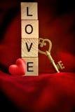 Ключ золота с деревянными письмами которые говорят влюбленность по буквам слова Стоковая Фотография