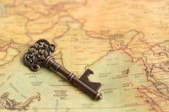 Ключ помещенный на карте мира Польза как концепция разрешая проблему каждой области Стоковые Изображения RF