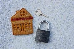 Ключ с замком и домом печенья на серой предпосылке Стоковая Фотография