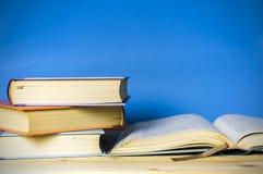 Книга в твердом переплете крупного плана изолированная на сини Стоковые Фото
