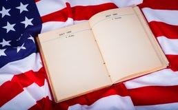 Книга года сбора винограда открытая на американском флаге красивом Стоковое Изображение RF