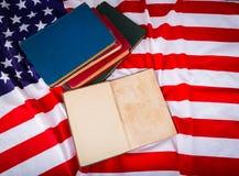 Книга года сбора винограда открытая на американском флаге освобождает Стоковое Изображение RF