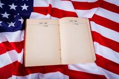 Книга года сбора винограда открытая на американском флаге освобождает Стоковые Изображения RF