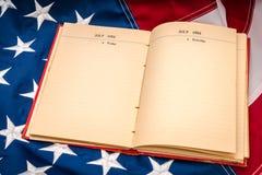 Книга года сбора винограда открытая на американском флаге Стоковые Изображения RF