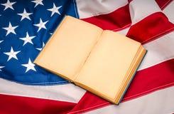 Книга года сбора винограда открытая на американском флаге Стоковые Фото