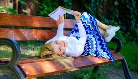 книга интересная Умный и довольно Умная дама ослабляя Девушка кладет парк стенда ослабляя с книгой, зеленой предпосылкой природы Стоковая Фотография RF