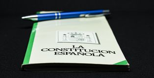 Книга испанской конституции с ручкой и графической белой предпосылкой Стоковая Фотография RF