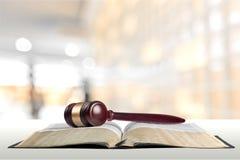Книга и деревянный молоток на таблице постамент правосудия принципиальной схемы 3d золотистый представляет маштаб Стоковые Изображения RF