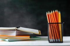 книга и карандаш на белой таблице чернят предпосылку доски с исследованием Стоковые Изображения