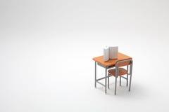Книга и миниатюрный уча стол стоковое изображение rf