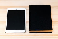 Книга и таблетка на таблице Стоковая Фотография