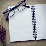 Книга и eyeglasses журнала на предпосылке холста Стоковое Фото