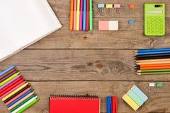 книга, калькулятор, блокнот, crayons и другие канцелярские принадлежности на коричневом деревянном столе Стоковая Фотография