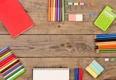 книга, калькулятор, блокнот, crayons и другие канцелярские принадлежности на коричневом деревянном столе Стоковое Фото