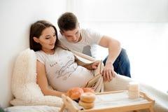 Книга лежать и чтения беременной женщины на кровати с супругом Стоковое Изображение