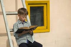 Книга мальчика изучая Стоковые Фотографии RF
