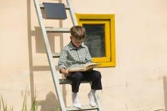 Книга мальчика изучая Стоковые Изображения RF