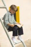 Книга мальчика изучая Стоковая Фотография