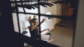 Книга молодого танцора девочка-подростка плача и срывая сидит на поле в зале внутри помещения Стоковое Изображение