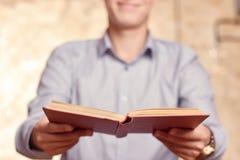 Книга молодого человека раскрытая удерживанием Стоковые Изображения RF