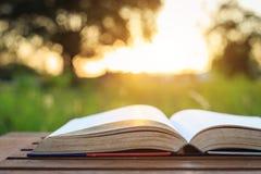 Книга на таблице во времени захода солнца Стоковые Изображения