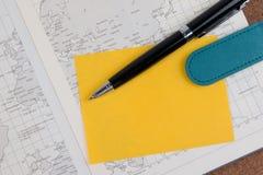 Книга дневника дела атласа мира с желтым бумажным примечанием Стоковые Изображения RF