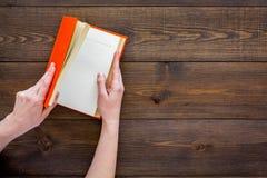 книга открытая Руки держат книгу hardback раскрытый на темном деревянном космосе экземпляра взгляд сверху предпосылки Стоковые Фотографии RF