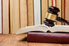 Книга по праву с деревянным молотком судей на таблице в зале судебных заседаний или офисе правоохранительных органов Стоковые Изображения RF