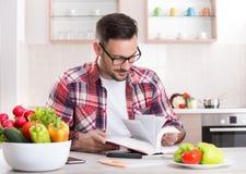 Книга рецепта чтения человека в кухне Стоковые Фото