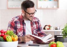 Книга рецепта чтения человека в кухне Стоковое Фото