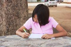 Книга сочинительства девушки в саде Стоковое фото RF